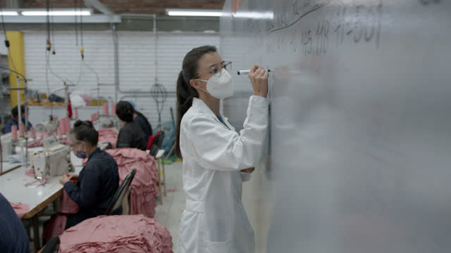 female supervisor writing production quantities confectioned at a textile factory on the white board - fashion industry stock videos & royalty-free footage