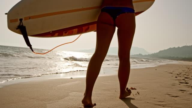 vídeos y material grabado en eventos de stock de slo mo mujer surfista con su tabla de surf a la playa - parte inferior