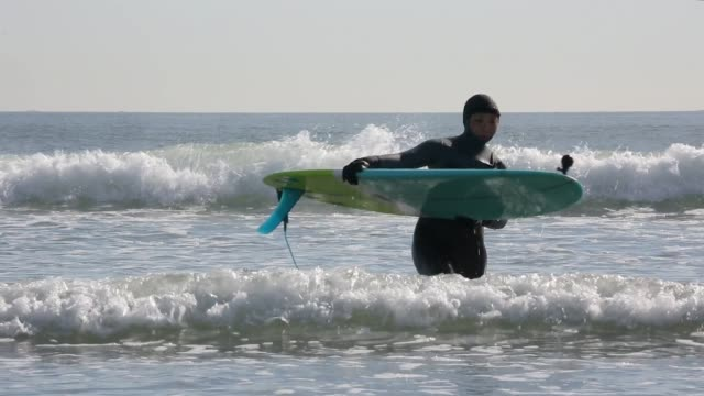 vídeos de stock, filmes e b-roll de feminina surfista com prancha de surf volta do oceano - traje de mergulho