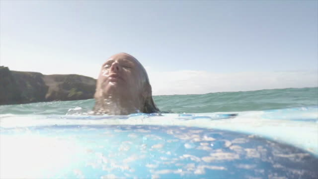 Female surfer emerges from sea