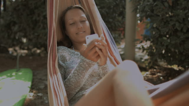 Female surfer laying in hammock in summer next to surfboard, looking at cell phone, swiping, smiling