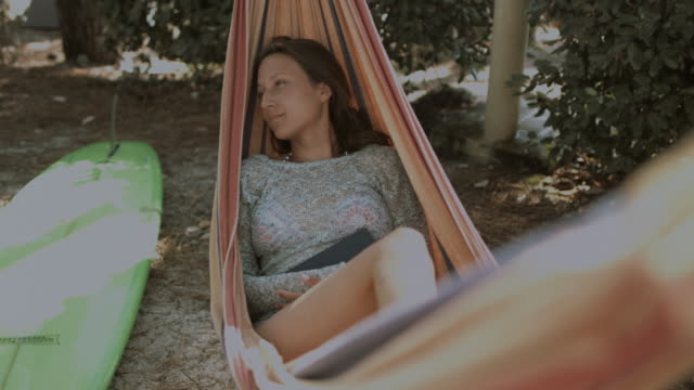 Female surfer laying in hammock in summer next to surfboard, relaxing, closing eyes