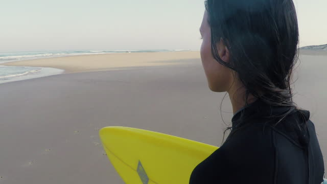 Female surfer looking at sea at deserted sandy beach at Atlantic ocean coast in the south of France.