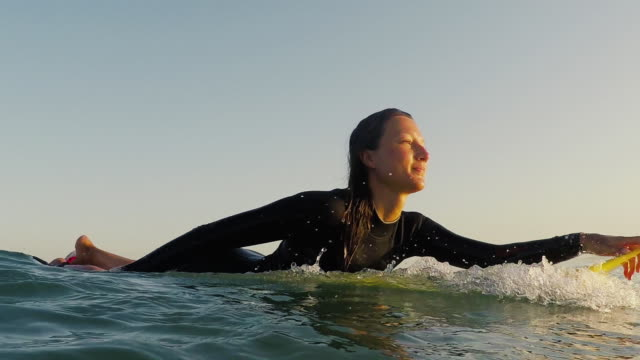 Female surfer paddling at sunset in sea at deserted sandy beach at Atlantic ocean coast in the south of France.