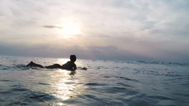stockvideo's en b-roll-footage met female surfer paddling on surfboard in bikini in ocean at sunset in southern france. - exploratie