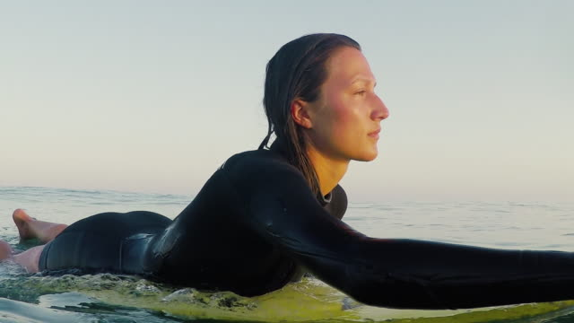 female surfer paddling on surfboard in sunset toward deserted sandy beach at atlantic ocean coast in the south of france. - floating on water stock videos & royalty-free footage
