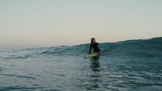 Female surfer paddling on surfboard in surf break in waves at deserted sandy beach at Atlantic ocean coast in the south of France.