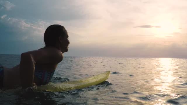vídeos de stock e filmes b-roll de female surfer paddling on yellow surfboard in bikini in ocean at sunset in southern france. - risco