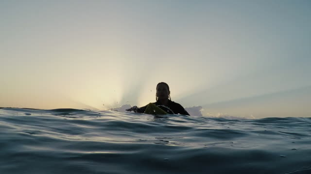 female surfer paddling out at sunrise at deserted sandy beach at atlantic ocean coast in the south of france. - anticipation stock videos & royalty-free footage