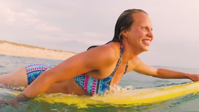vídeos de stock e filmes b-roll de female surfer paddling out in bikini on yellow surfboard smiling in atlantic ocean in southern france. - grupo multiétnico