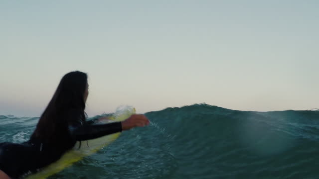 female surfer paddling over waves on surfboard at sunrise at deserted sandy beach at atlantic ocean coast in the south of france. - aquitaine stock-videos und b-roll-filmmaterial