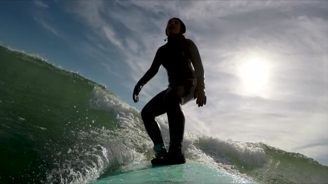 female surfer riding ocean waves - wetsuit stock videos & royalty-free footage