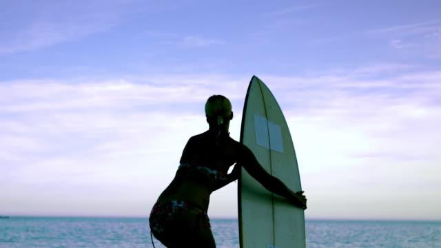 Female surfer running towards the ocean