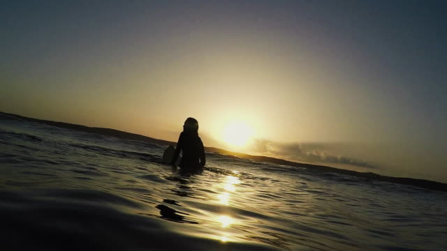 female surfer sitting on surfboard at sunrise in surf break and waves at deserted sandy beach at atlantic ocean coast in the south of france. - surfbrett stock-videos und b-roll-filmmaterial