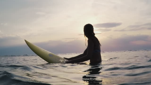 Female surfer sitting on surfboard in bikini at sunset in Atlantic ocean in the South of France