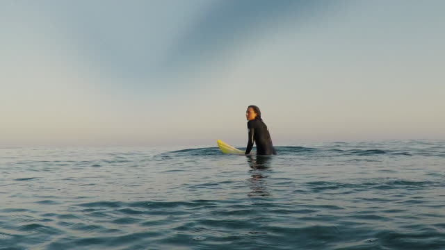 Female surfer sitting on surfboard in surf break at deserted sandy beach at Atlantic ocean coast in the south of France.