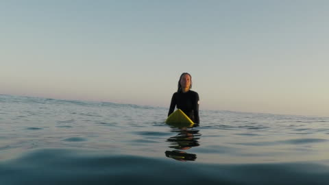 female surfer waiting for waves sitting on surfboard in surf break at deserted sandy beach at atlantic ocean coast in the south of france. - waiting stock videos & royalty-free footage