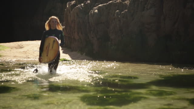 Female surfer walking through rock pool
