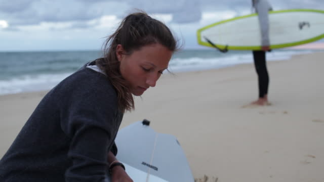 Female surfer waxing surfboard at beach in southern France
