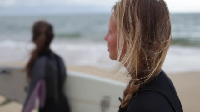 female surfers with surfboards walking along beach in france. - hairstyle stock videos & royalty-free footage