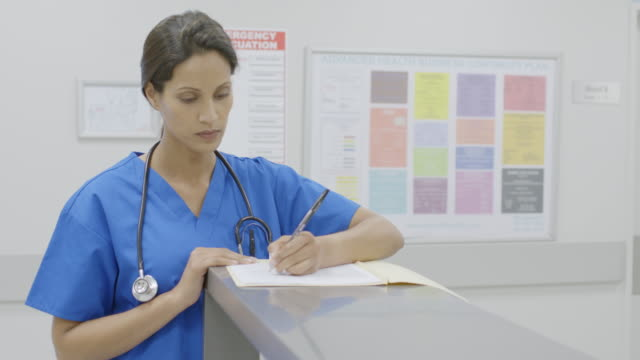 female surgeon filing medical form in hospital - infermiere video stock e b–roll