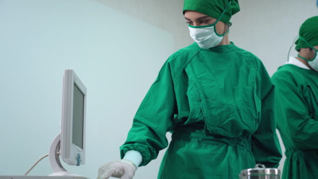 female surgeon operating the monitor - operating gown stock videos & royalty-free footage