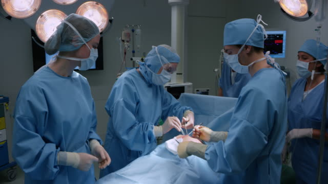 Female surgeon performing operation on patient