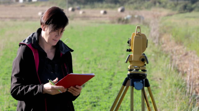 vídeos de stock e filmes b-roll de female surveyor writing down notes and standing by theodolite - inspetor profissão