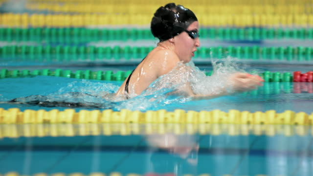 SLO MO TS Female swimmer competing in breaststroke style