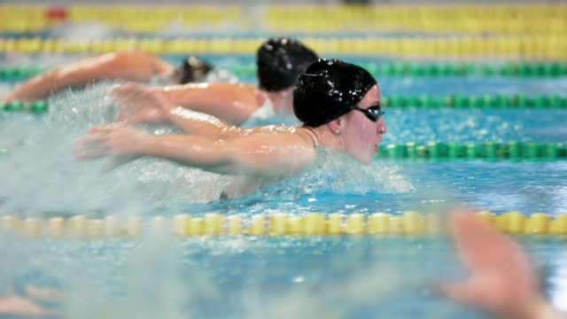 SLO MO TS Female swimmer competing in butterfly style competition