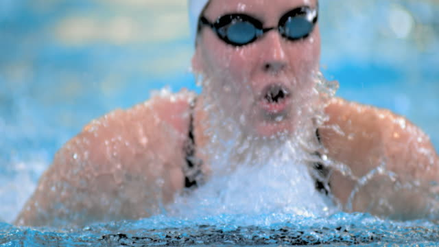 SLO MO Female swimmer dives in breaststroke style