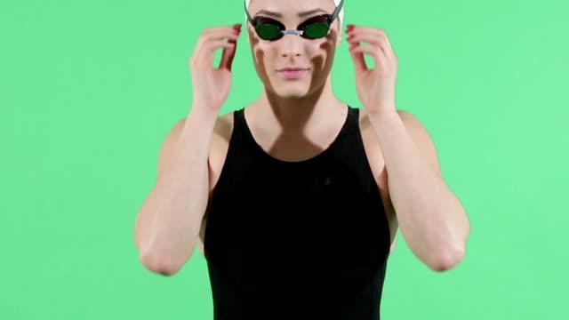 vídeos de stock, filmes e b-roll de feminino nadador fixação seus óculos verdes de fotografar - óculos de natação