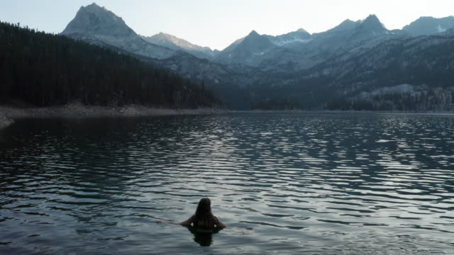 female swimmer in lake surrounded by snow-covered mountains - mammoth lakes video stock e b–roll