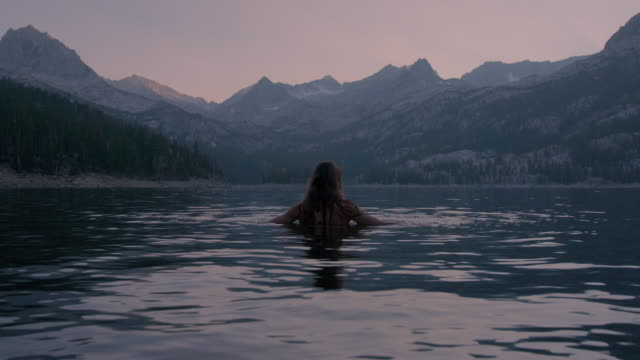 stockvideo's en b-roll-footage met female swimmer in lake surrounded by snow-covered mountains - californian sierra nevada