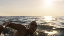SLO MO TS Female swimmer swimming forward crawl in the choppy sea in sunshine