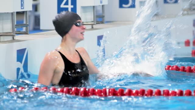 stockvideo's en b-roll-footage met ts female swimmer touching the wall and celebrating her win - binnenbad