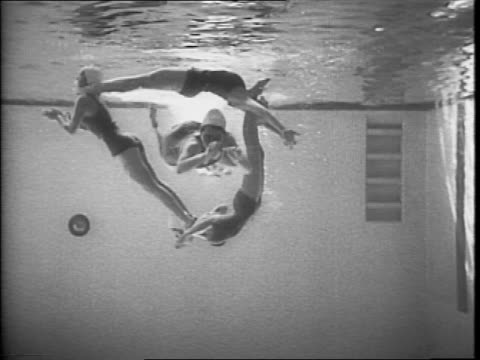 Female swimmers diving into an indoor pool / women swimming to the surface of the water / women swimming in a circle as seen from under the water /...