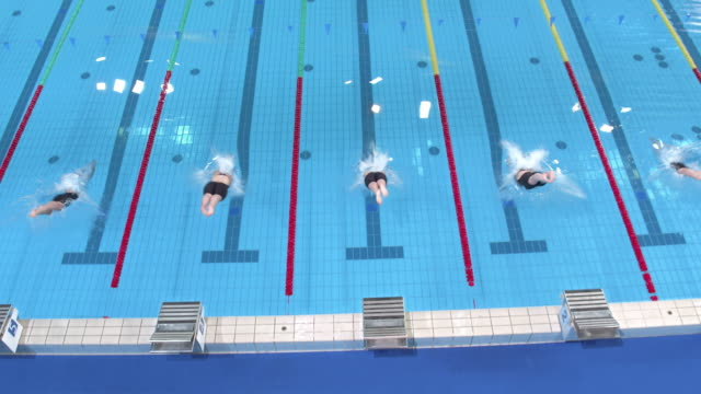AERIAL Female swimmers diving into the water in breaststroke competition