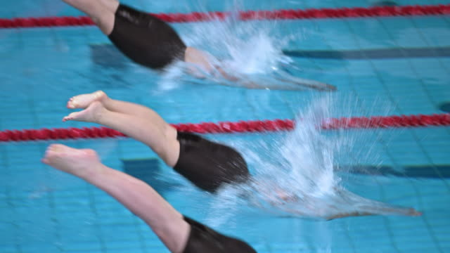 slo mo female swimmers in competition diving off starting blocks - diving into water stock videos & royalty-free footage
