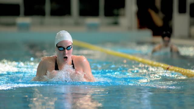 stockvideo's en b-roll-footage met slo mo female swimming in breaststroke technique - binnenbad