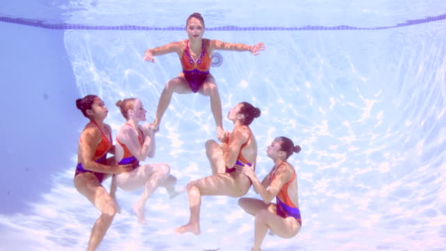 MS Female synchronized swim team performing lift during routine underwater view