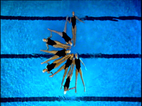 stockvideo's en b-roll-footage met female synchronized swimmers change from star formation into a single line then split away - versmelten