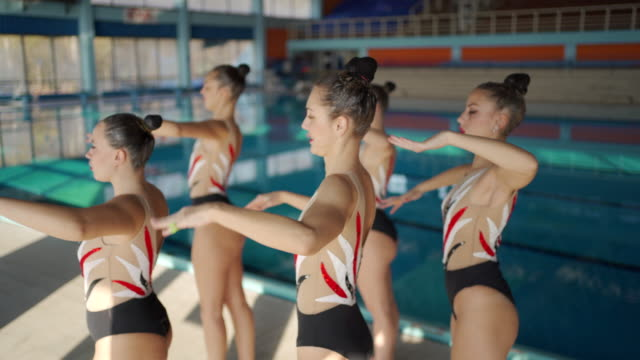 female synchronized swimmers practising routine by poolside - woman swimming costume stock videos & royalty-free footage