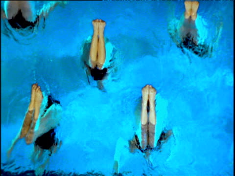 Female synchronized swimmers stick legs out of water in dance maneuver