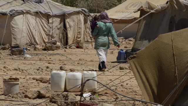 female syrian refugee walks through camp with tents toddler on hip older woman picks up big stick near tent - シリア難民問題点の映像素材/bロール