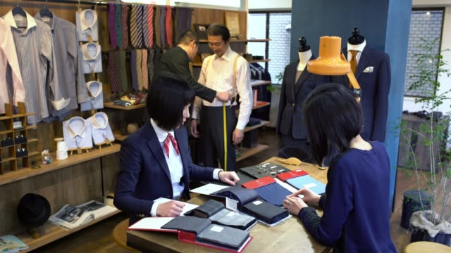 female tailor in a high end suit shop talking to a customer - customised stock videos & royalty-free footage