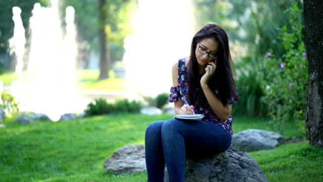 Female talking on the phone in the park and writing in the notebook