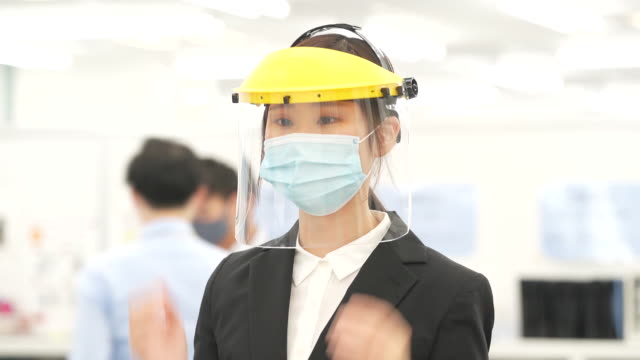 vidéos et rushes de female teacher adjusts a face shield as she prepares for a lesson at riso kyoiku co. tomas school in the ikebukuro district of tokyo, japan, on... - enseignante