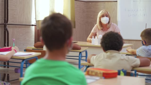 vídeos de stock e filmes b-roll de female teacher and school kids with protective face masks at classroom during coronavirus pandemic - criança de escola primária