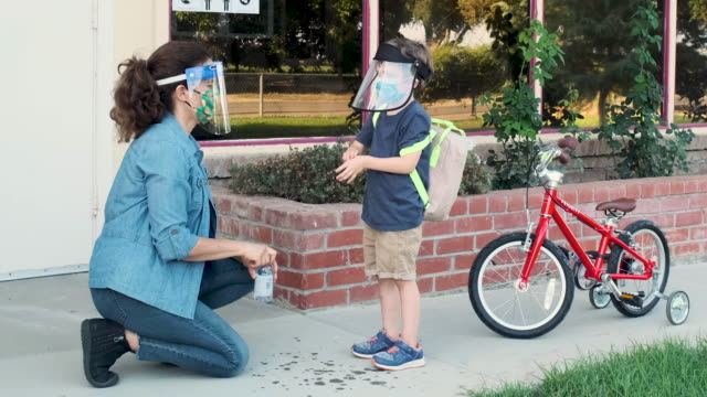 female teacher applying disinfectant gel on preschool student hands - preschool building stock videos & royalty-free footage